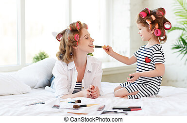 Mother and baby daughter in curlers  doing makeup on bed