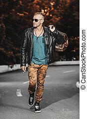 walking on a highway - Handsome brutal man in leather jacket...