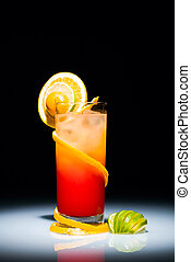 Tequila sunrise cocktail with slice of orange and lime