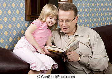 Reading a book - Portrait of a father sitting on the sofa...