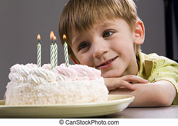 Birthday - Happy blond boy with birthday cake looking at the...