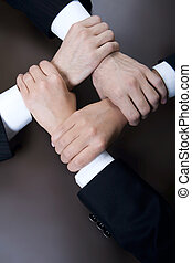 Unity - Isolated on black four crossed human hands in...