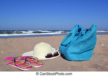 Summer concept with bag, hat, glasses and flip flops on beach