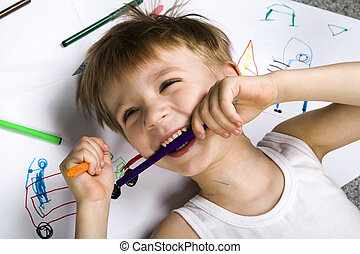 Inspiration - Laughing boy lying on his drawing with...
