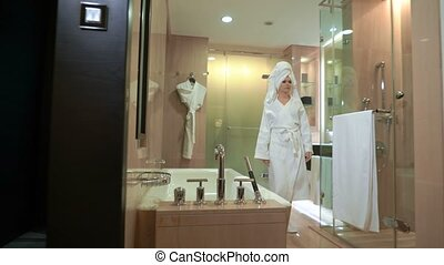 beautiful young woman after shower with a towel on her head in white coat sits down in armchair at home or hotel room, drinks hot tea or coffee. Sexy girl is relaxing, resting, drinking, taking a cup
