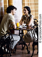 The first date - Young couple in old cafe sitting at the...