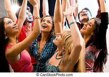 Elation - Portrait of laughing people raising their hands