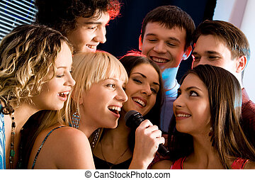 Karaoke party - Attractive woman is holding the microphone...