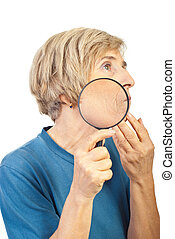 Senior woman analyze her wrinkles with loupe - Senior woman...
