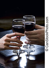 Night date - Two hands holding red wine glasses over the...