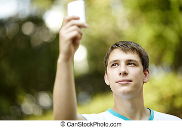 teen with palmtop - portrait of young man with gadget...