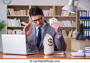 Businessman gambling playing cards at work