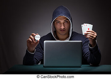 Young man wearing a hoodie sitting in front of a laptop...