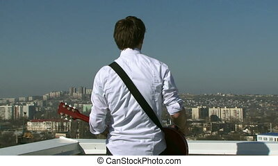 Musician drink coffee on the roof - Male musician with a...