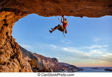 Male climber on overhanging rock against beautiful view of...
