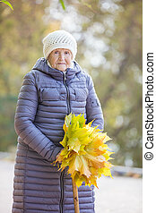 Senior woman with bunch of autumn leaves walking in park