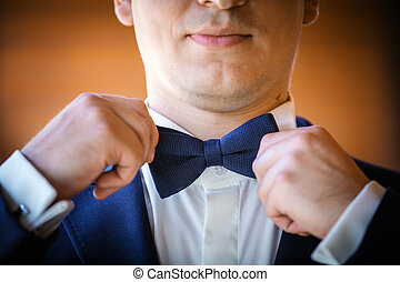 Closeup of young man adjusting bow-tie on his wedding day
