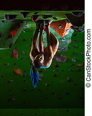 Young woman bouldering along ceiling in climbing gym - Young...
