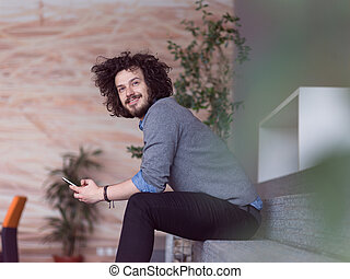 Young casual businessman holding smartphone in the startup...