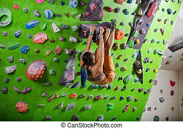 oung woman bouldering in climbing gym