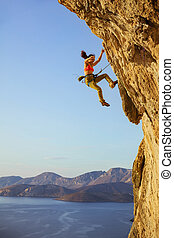 Female rock climber falling off cliff while lead climbing,...