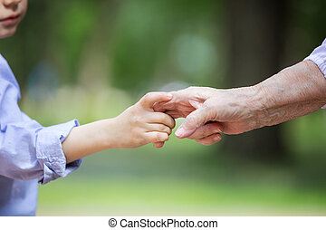 Young boy holding great grandmother's hand