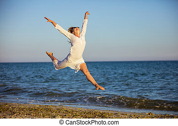 Woman jumping with joy on beach