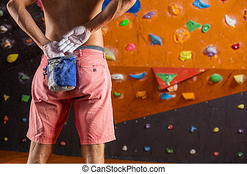 Rock climber putting chalk on hands to prepare for...