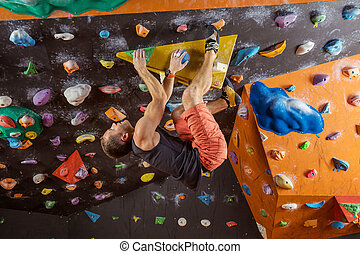 Young man bouldering in indoor climbing gym, trying to solve...