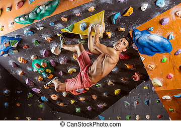 Young man bouldering in indoor climbing gym, looking at next...