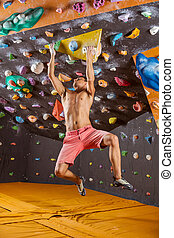 Young man bouldering in indoor climbing gym, struggling to...