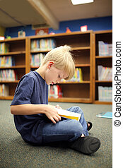 Elementary School Aged Child Reading Book at Library - A...