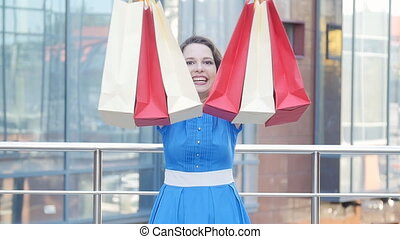 Young happy woman carrying shopping bags - Young happy woman...