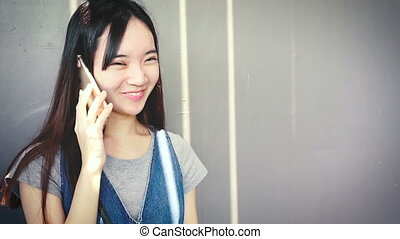 Attractive young asian chinese woman talking on smart phone