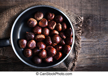 Ripe chestnuts in a frying pan on old wooden table close up...