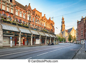 Amsterdam street with cathedral Westerker at sunrise,...