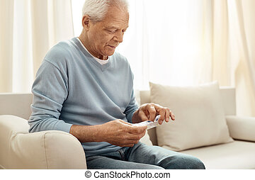 Cheerless senior man holding a pill organizer