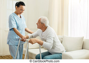 Positive nice woman working as a caregiver - Healthcare...