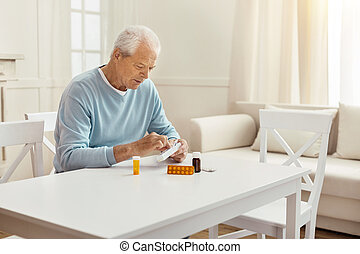 Nice elderly man holding a box with pills