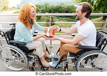 Positive wheelchaired couple holding a present - Little...