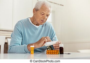 Unhappy cheerless man taking medicine