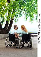 Rear view of a nice disabled couple resting in the park -...
