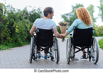 Rear view of a senior disabled couple resting in the park -...
