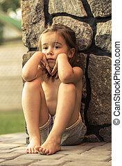 sad little girl - sad little cute girl sits on the pavement...