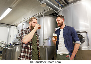 men testing non-alcoholic craft beer at brewery -...