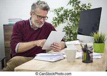 Cheerful man browsing websites on his digital tablet