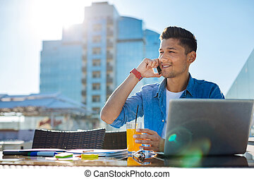 Joyful young man talking on phone outdoors - Happy to hear...