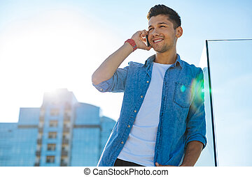 Cheerful guy having phone call in downtown - Happy to hear...