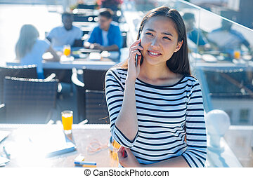 Cheerful girl talking on phone outdoors - Friendly...