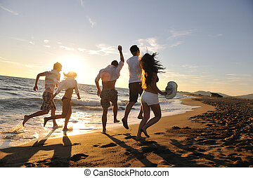 people group running on the beach - happy young people group...